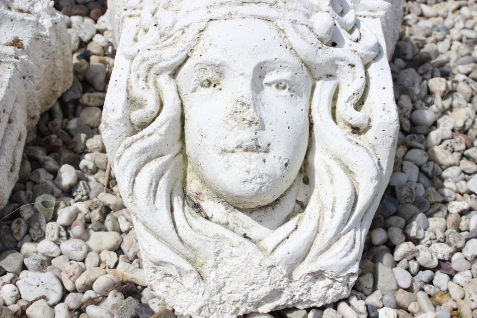 Oud betonnen beeld dames hoofd