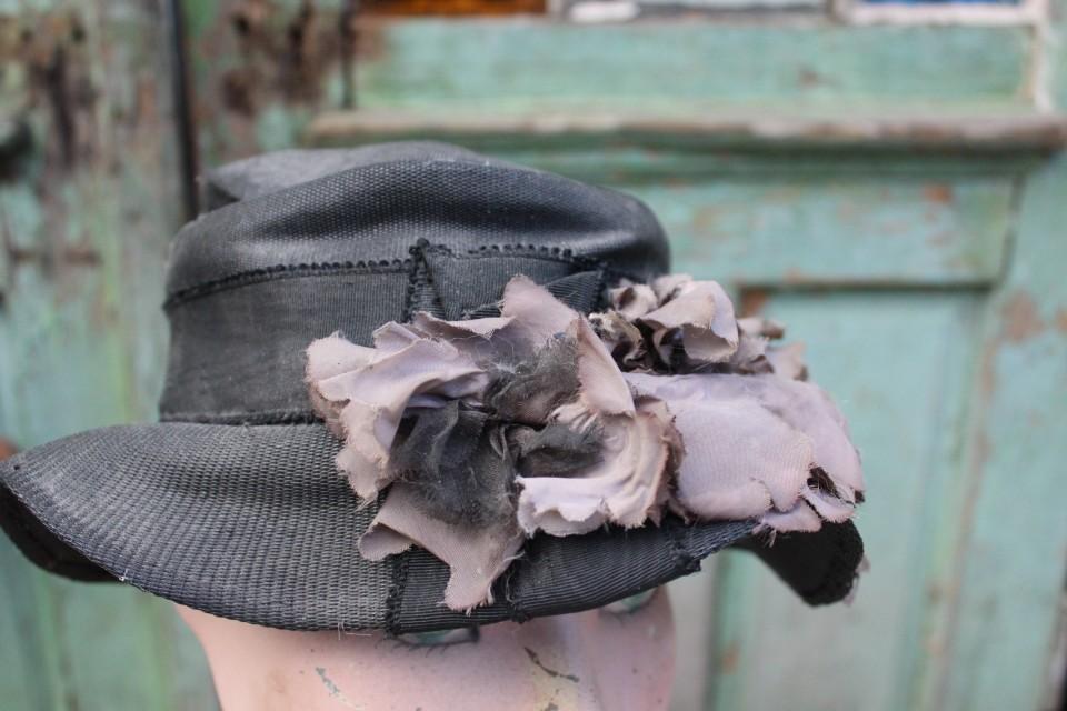 Oude zwarte hoed met corsage